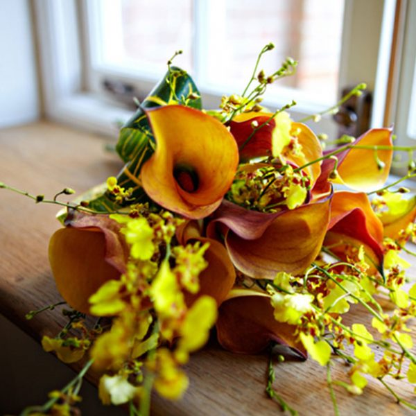 An autumnal floral bouquet with orange and cream wedding flowers
