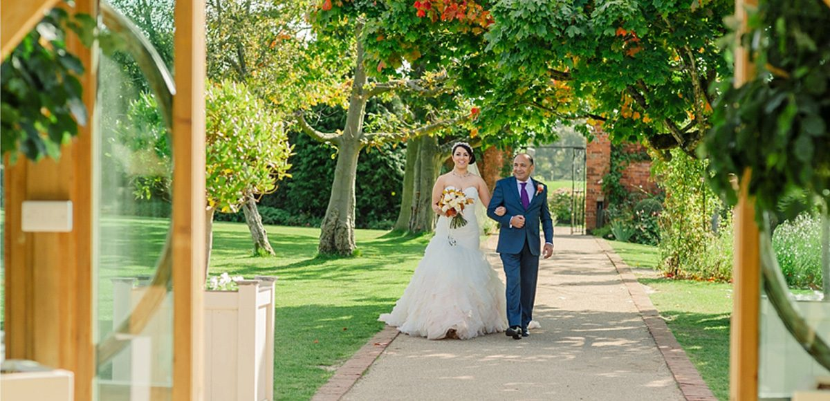 The father of the bride walking his daughter down the garden aisle at Gaynes Park in Essex