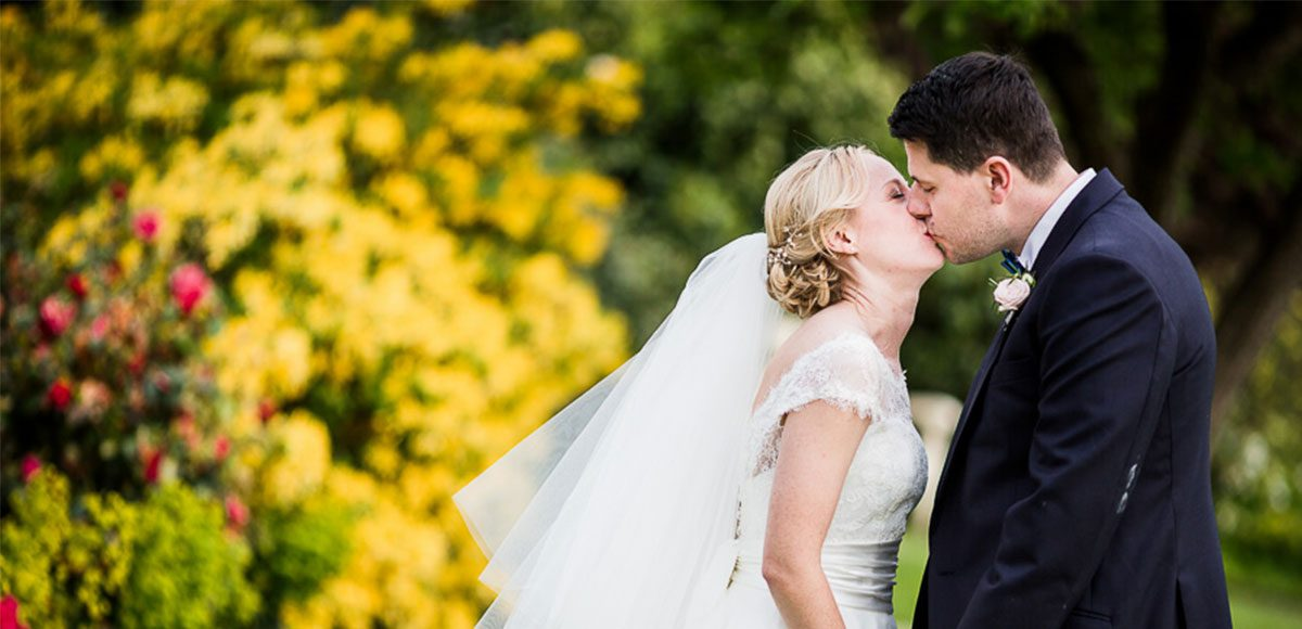 Bride and groom kissing in the gardens of Gaynes Park after their wedding ceremony