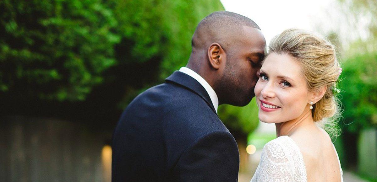 Bride and groom posing in the grounds of Gaynes Park wedding venue in Essex