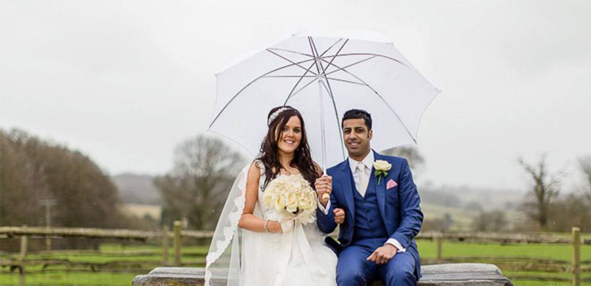 Bride and groom posing with umbrella in the grounds of Gaynes Park