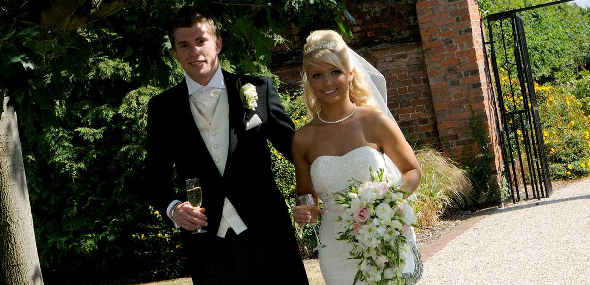 Bride and groom walking down the Long Walk enjoying the summer flowers