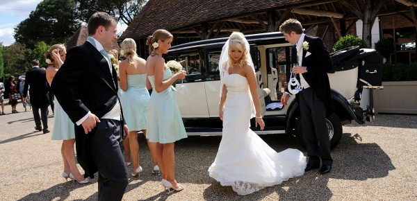 Bride and groom by their wedding transport – barn hire Essex
