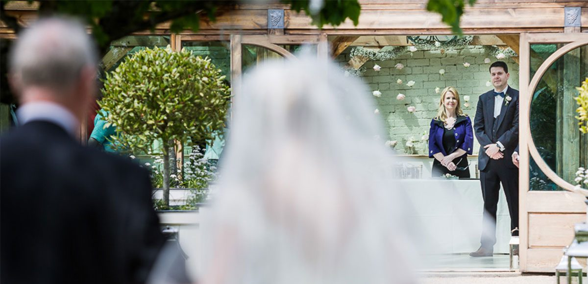 Bride taking the Long Walk into the Orangery at Gaynes Park for a wedding ceremony