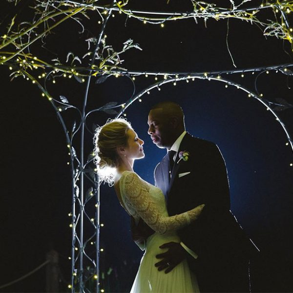 Bride and groom posing for photos in gardens of Gaynes Park at night