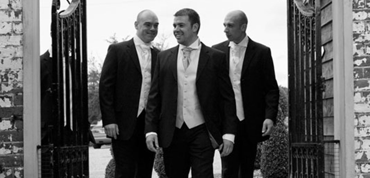 Groomsmen under the arch at the Essex wedding venue