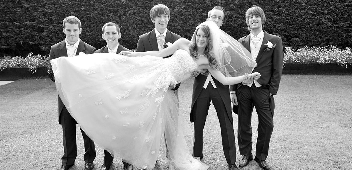 The bride being held up by the groom and his groomsmen in a fun wedding photo