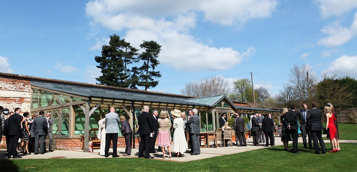 Wedding guests enjoying the sun outside the Orangery at Gaynes Park – venues in Essex