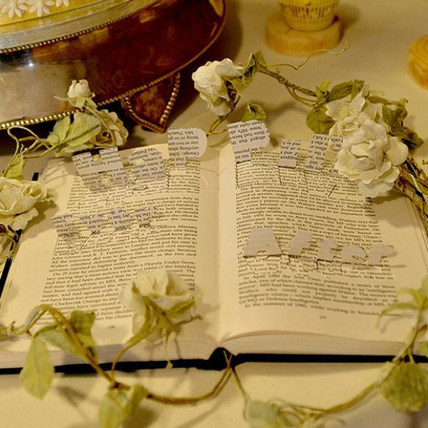 A book decoration for use on the wedding cake table with Happy Ever After cut out of the pages
