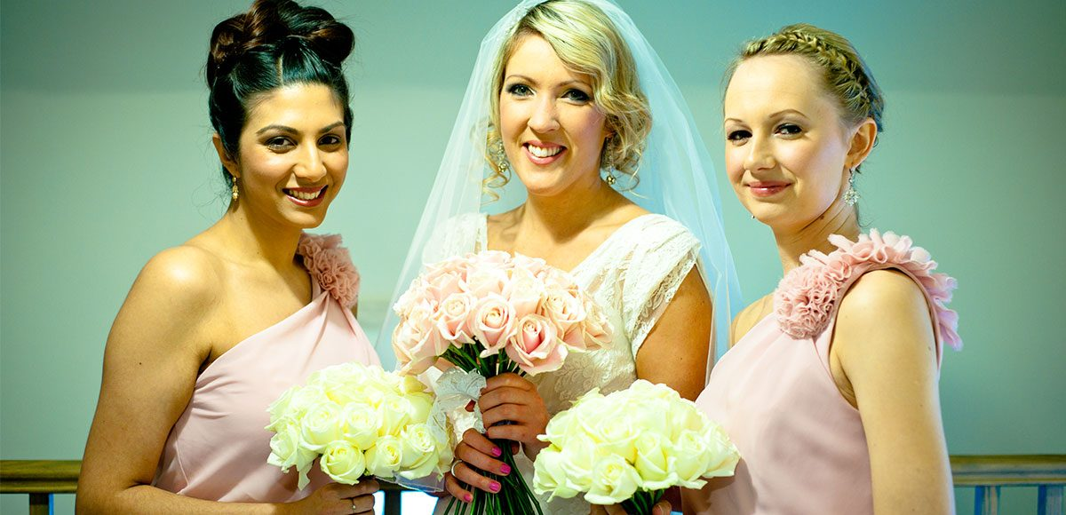 Bride and bridesmaids dressed in pink ready for a Gaynes Park wedding ceremony