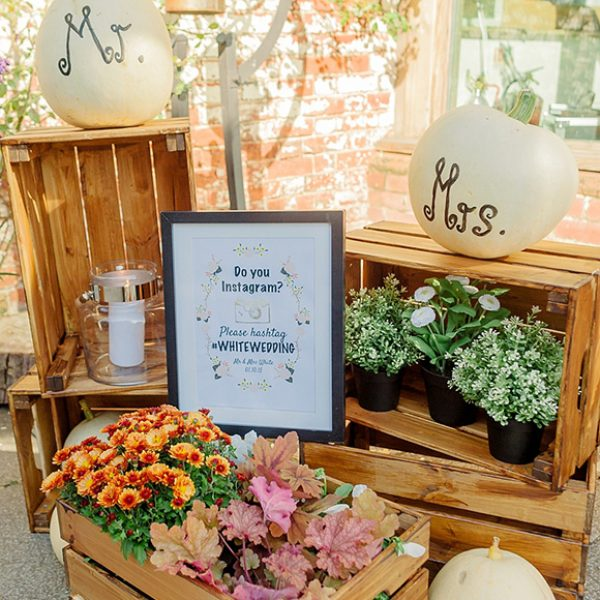Rustic crates create a stunning autumnal feel background for flowers and pumpkin wedding decorations