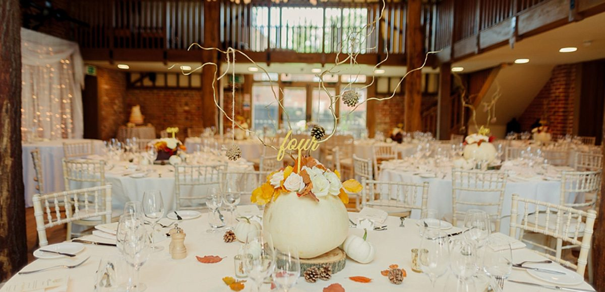 The Mill Barn decorated for the wedding reception with white pumpkin table centrepieces