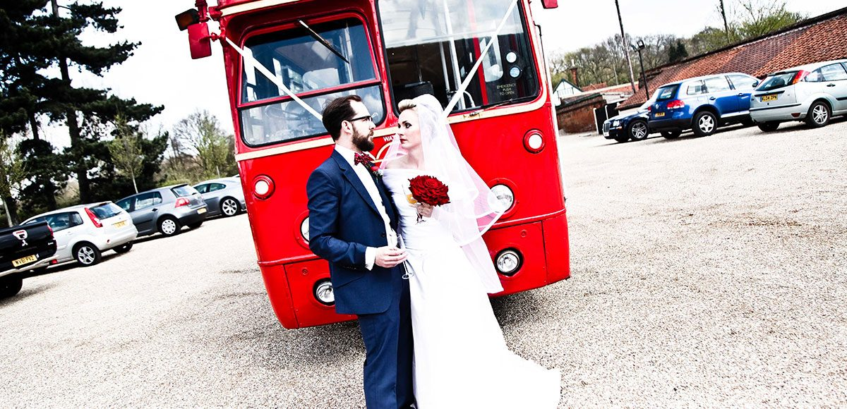 Bride and groom in front of their red bus wedding transport – Essex wedding venues