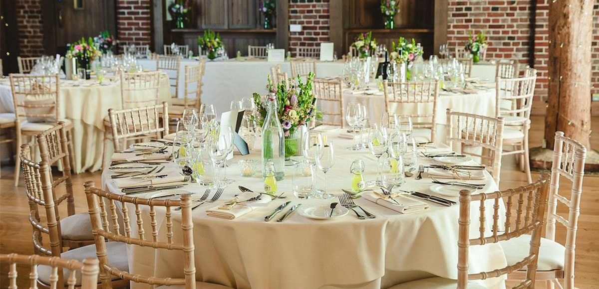 Table decorations set up for a barn wedding reception in Essex