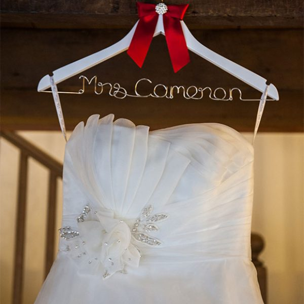 Wedding dress hung on a personalised hanger ready for wedding ceremony