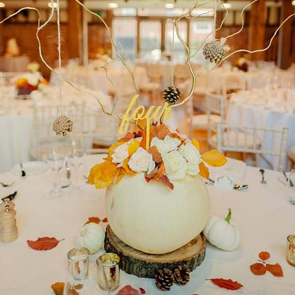 A rustic wedding centrepiece using white pumpkins