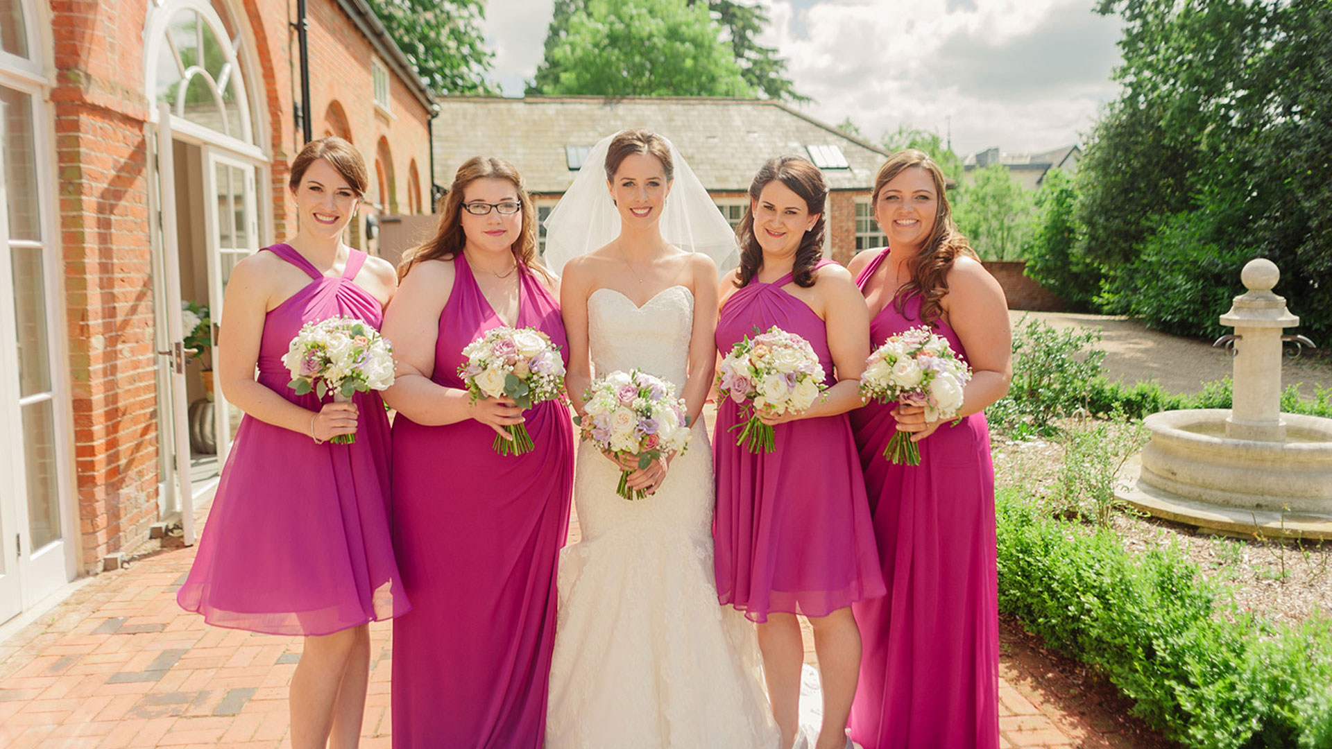 A beautiful bridesmaid stands with her bridesmaids outside of the Coach House - wedding venues in Essex