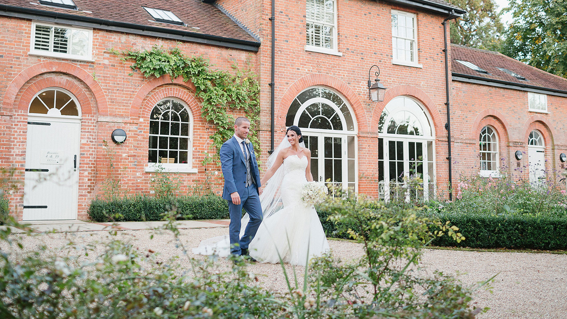 Bride and groom walk together at Gaynes Park stunningly contemporary wedding guest accommodation