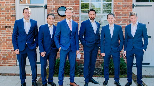 A groom and his groomsmen look stylish in blue suits ready for a barn wedding