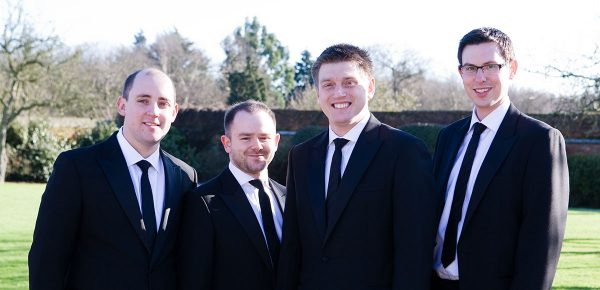 Groomsmen posing for a photo in the gardens