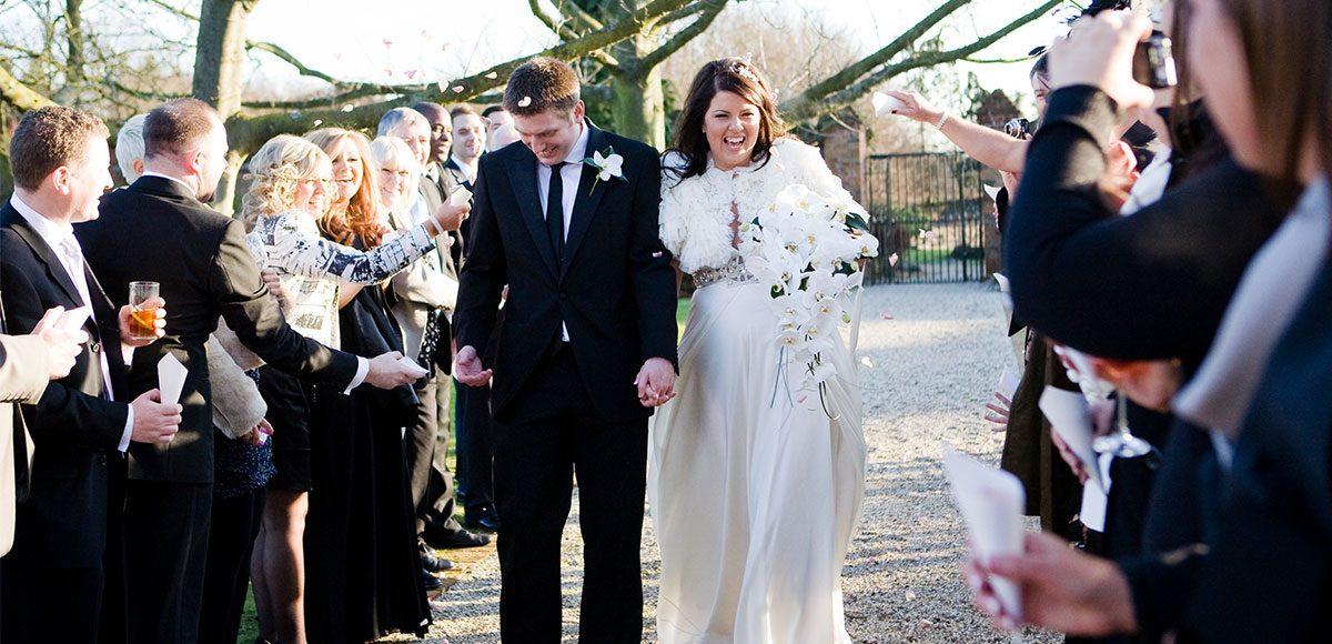 Wedding guests throw confetti during winter wedding at Gaynes Park