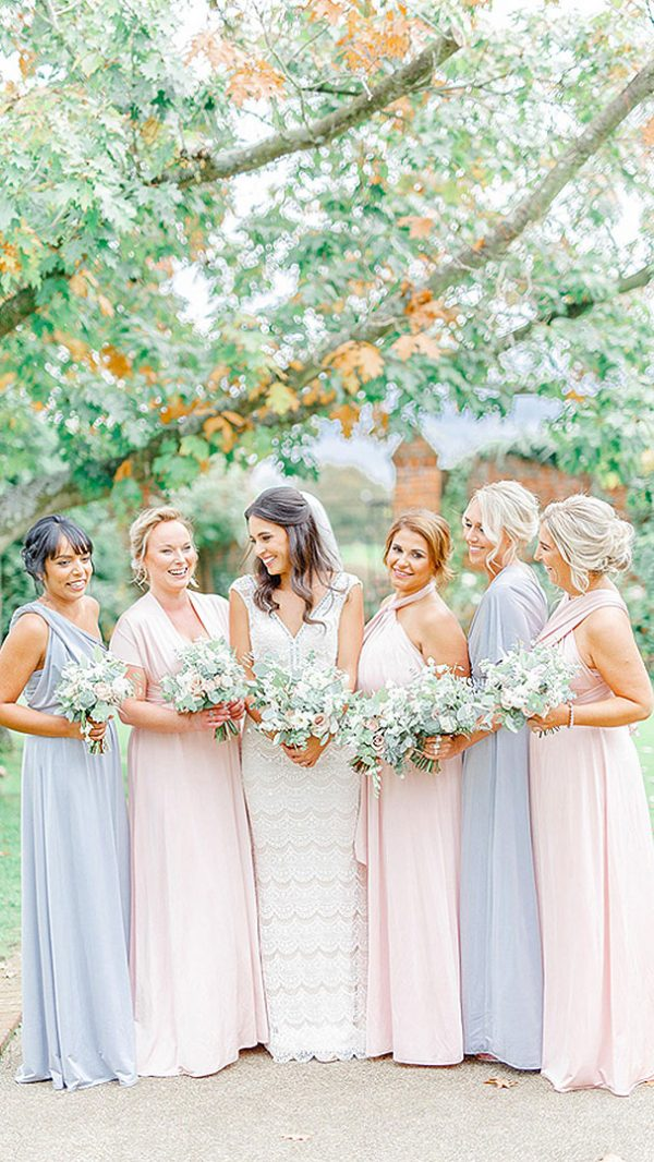 A bride smiles with her bridesmaids dressed in pale blue and pink bridesmaid dresses - wedding ideas
