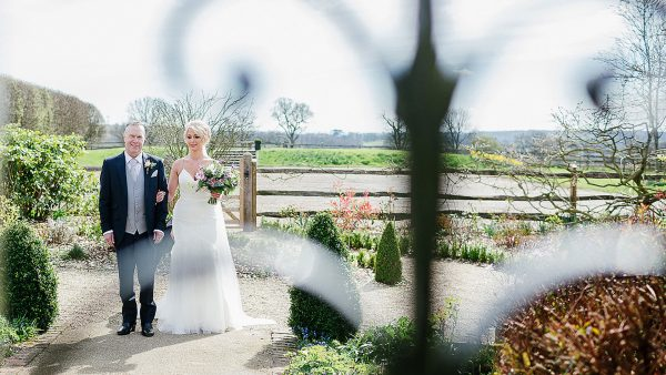 A bride and her father begin their walk down the wedding aisle - wedding ceremony venues in Essex