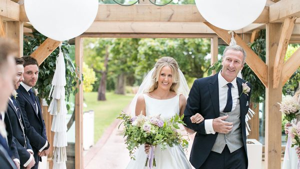 A bride and her father enter the Orangery decorated with large white balloons - wedding decorations
