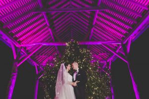 A couple stand in front of a Christmas Tree in the Gather Barn - winter wedding decorations