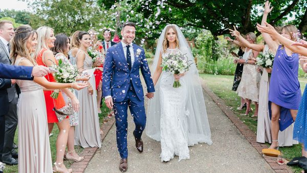 A bride and groom are covered with confetti as they enjoy this special moment in the Walled Garden