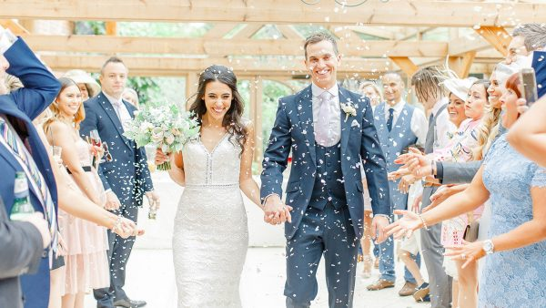 A bride and groom are congratulated in the ceremony barn at this unique wedding venue in Essex