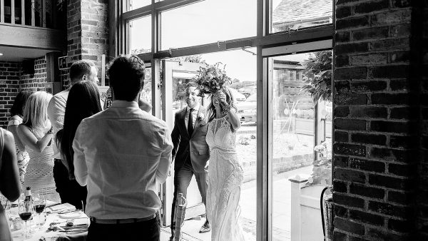 A bride and groom make their entrance into the Mill Barn after saying their marriage vows earlier