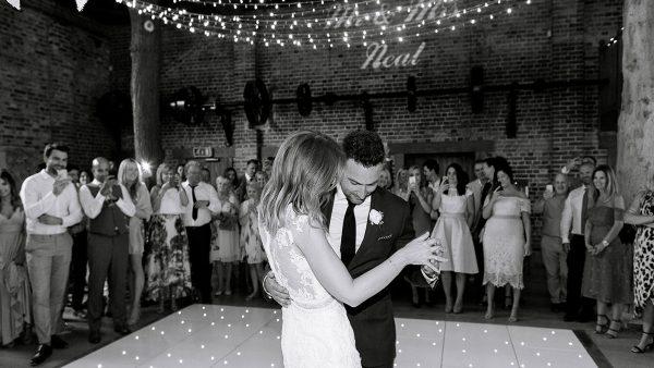 A bride and groom dance their first wedding dance on a white dancefloor inside the beautiful barn wedding venue