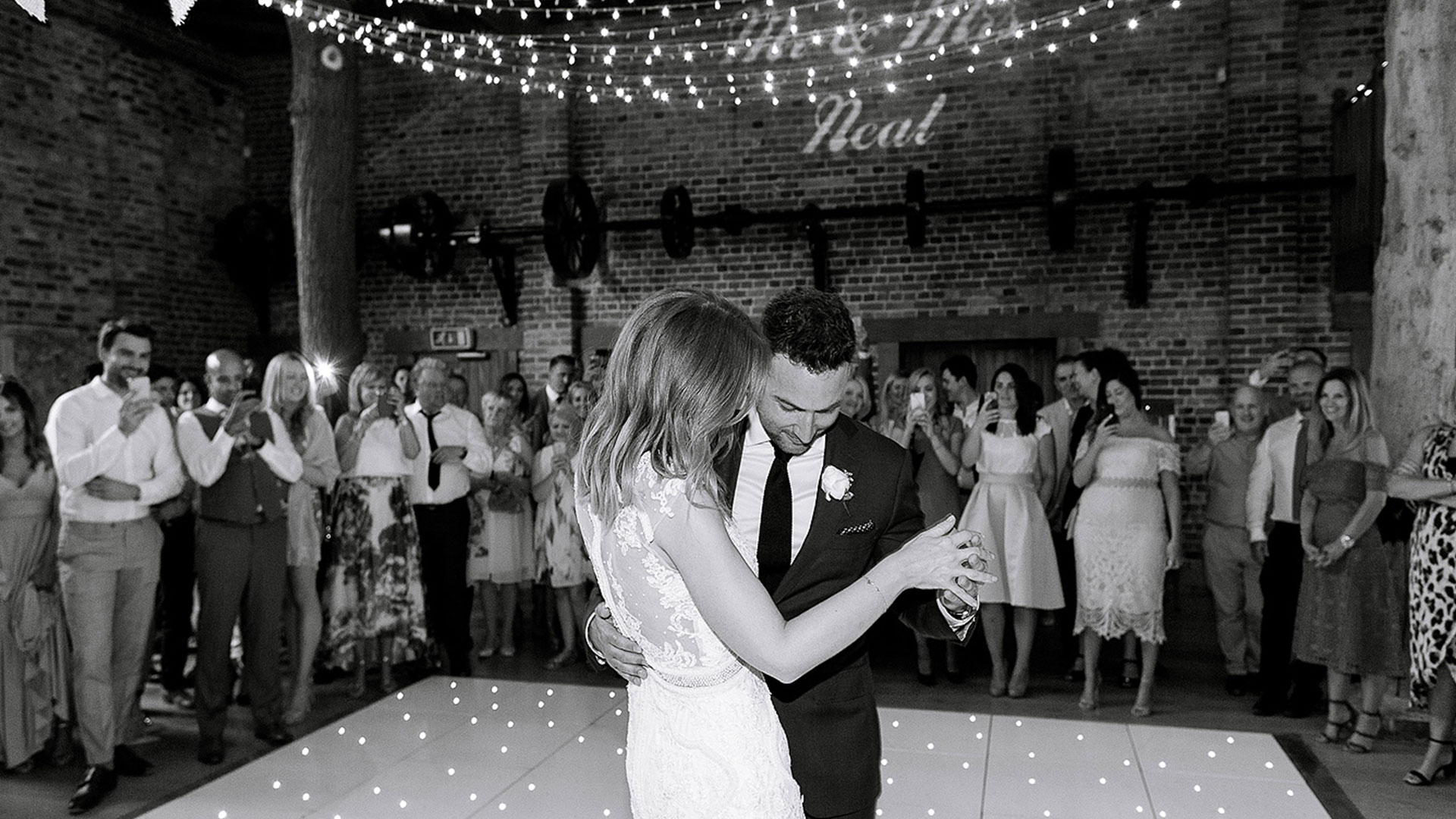 A bride and groom dance their first wedding dance on a white dancefloor inside the beautiful barn wedding venue