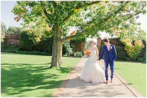 A bride and groom enjoy the Walled Garden during their autumn wedding at Gaynes Park