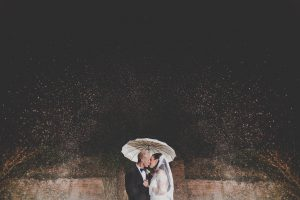 A couple kiss under falling snow at Gaynes Park winter wedding venue in Essex