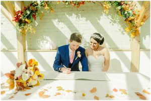 A happy couple sign the register after exchanging marriage vows in the wedding ceremony barn