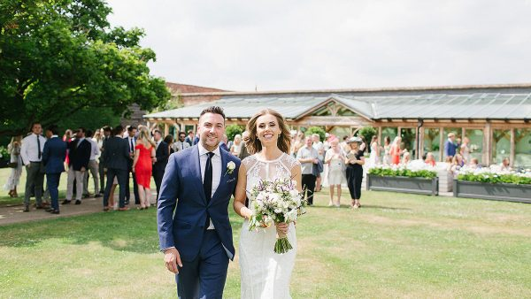 A bride and groom smile as they enjoy a drinks wedding reception in the Walled Garden