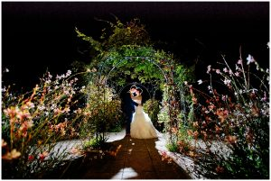 A couple stand under the garden wedding pavilion with its twinkling fairy lights