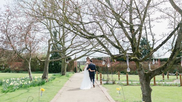 A bride and groom steal a moment in the Walled Garden which has year-round colour - garden weddings