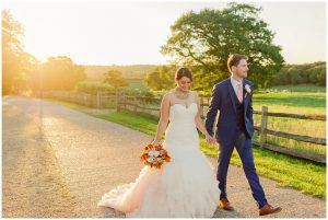 A bride carries a gorgeous autumn wedding bouquet in the evening sun at Gaynes Park