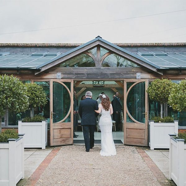 The bride and her father make their way down the long garden aisle to the orangery at the end of the walled garden path