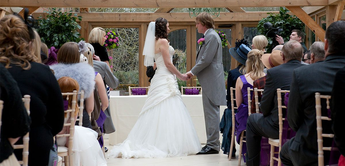 Bride and groom taking their vows in the Orangery – wedding venues in Essex