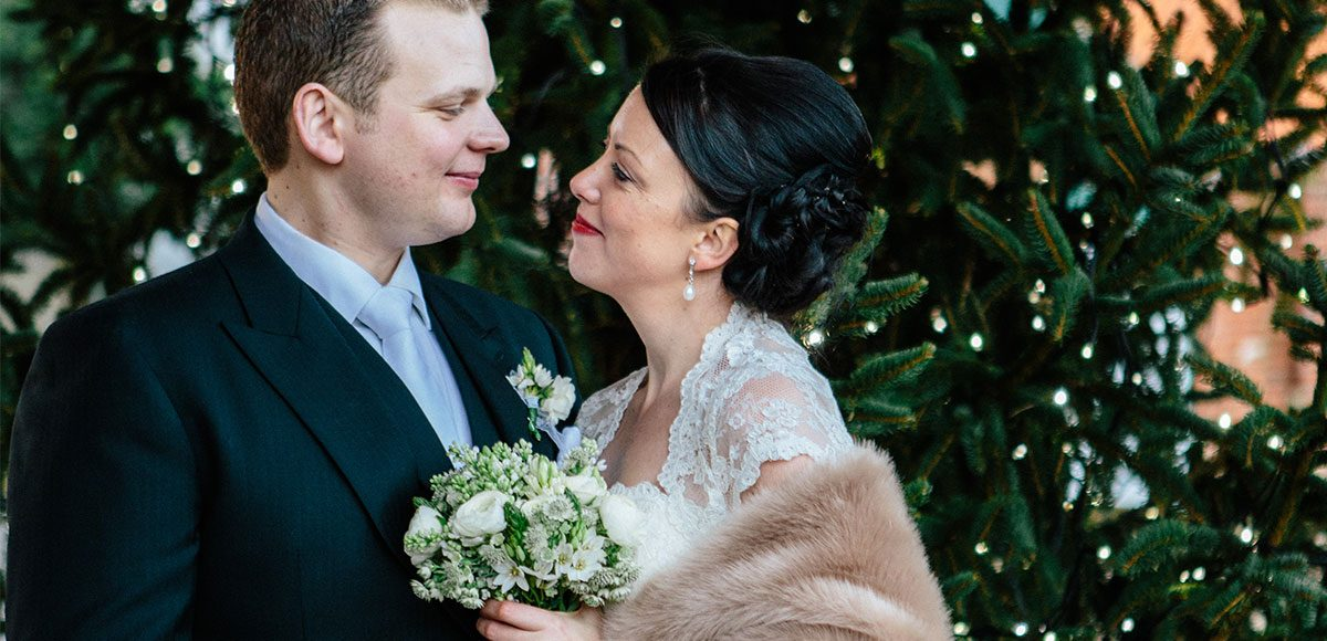 Bride and groom in front of the Christmas tree – wedding venues in Essex.
