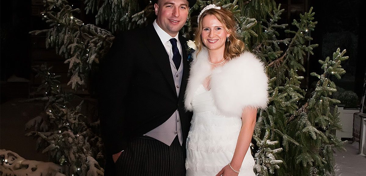 Bride and groom under the Gather Barn with a Christmas tree.