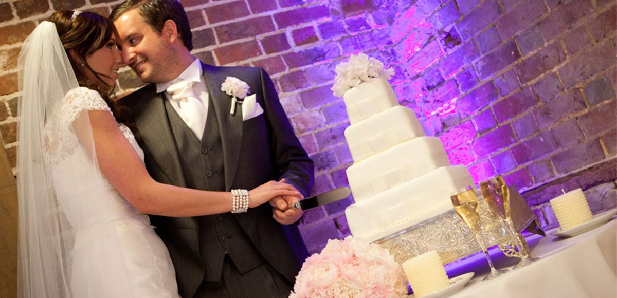 Bride and groom cutting the cake – barn venue hire Essex