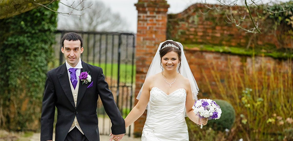 Bride and groom exploring the gardens of their Essex wedding venue.