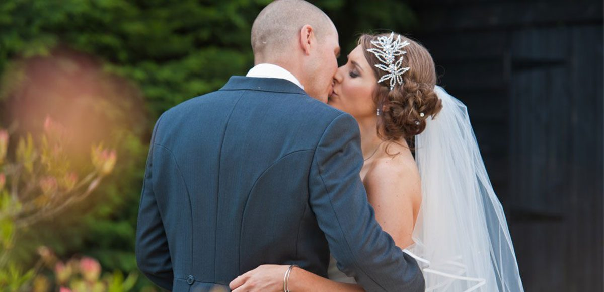 Bride and groom share a moment in the gardens of their Essex wedding venue