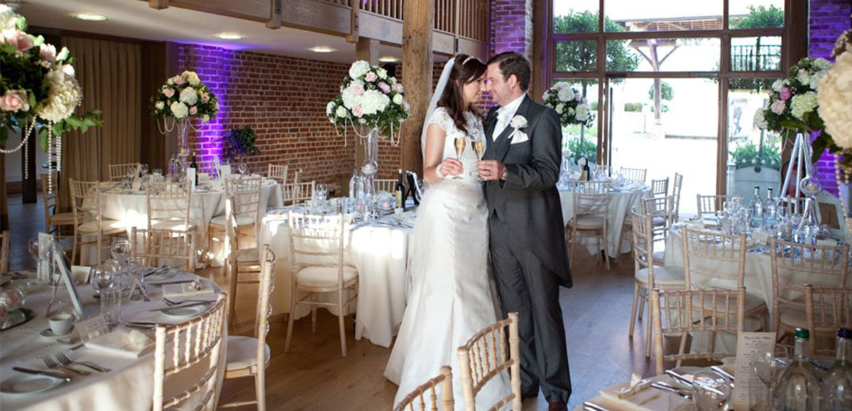 Bride and groom enjoy champagne inside the Mill Barn at Gaynes Park – wedding barns Essex