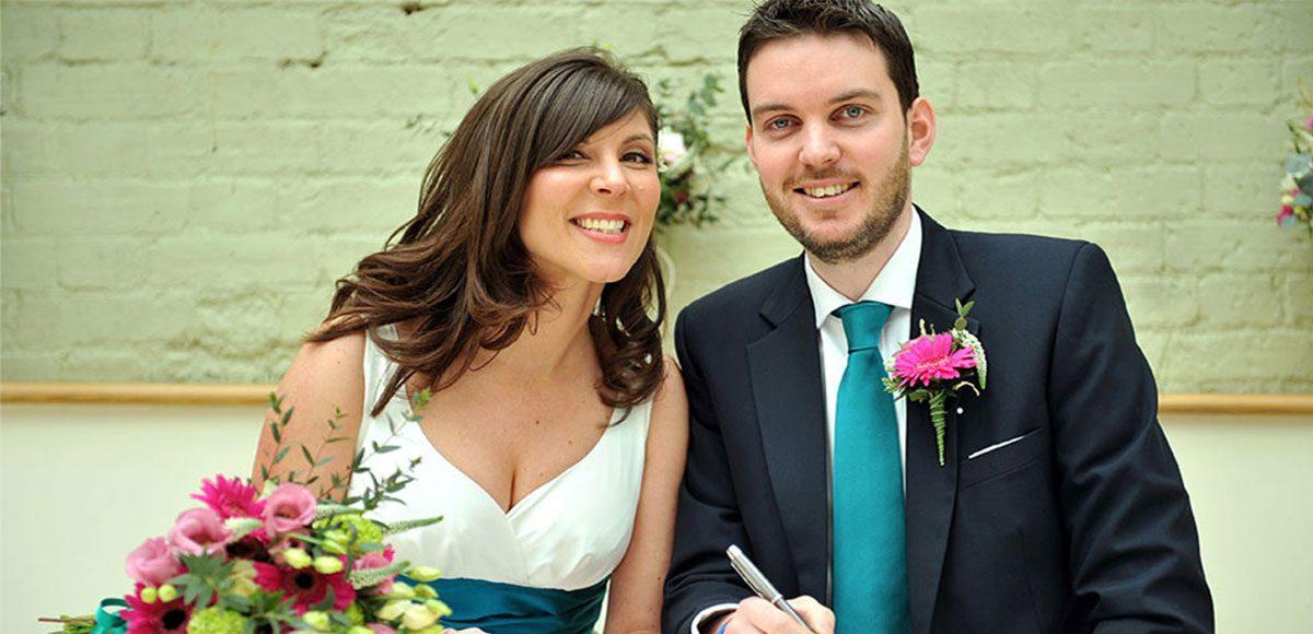 Bride and groom signing the register at Gaynes Park wedding venue in Essex